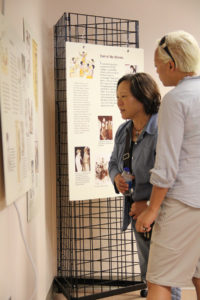 "Visitors explore the ""GIs and the Kids"" exhibition at the Bel Air Library which is on display through July 27."
