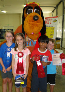 Winners from the 3rd and 4th grade category at the Literary Spelling Bee pose with Tales, the Harford County Public Library mascot. First Place- Lizzy Kelly, Second Place Tie- Elysa Puglionesi, Aman Tripatchi and Jeremy Jestel.