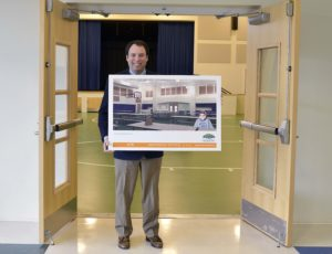 Dr. Gray Smith with an artist rendering of the future Dining Hall